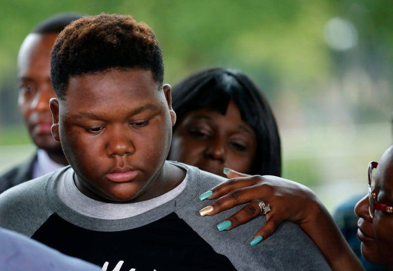 Cameron Sterling, son of Alton Sterling, is comforted as he listens to family and attorneys speak following a meeting with the U.S. Justice Department at federal court in Baton Rouge, La., Wednesday, May 3, 2017. An investigation into the police shooting death of Alton Sterling in Baton Rouge found that there was not enough evidence to prove that the white officers acted unreasonably and willfully, a federal prosecutor said Wednesday.