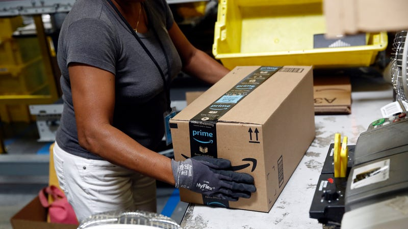 An Amazon worker applies tape to a package before shipment at an Amazon fulfillment center in Baltimore.