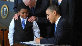 President Barack Obama signs the health-insurance-reform bill as 11-year old Marcelas Owens of Seattle looks on with Vice President Joe Biden on March 23, 2010, in the East Room of the White House.MANDEL NGAN/AFP/Getty Images