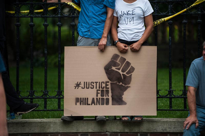 A couple hold a sign, protesting the police killing of Philando Castile, outside the governor's mansion July 7, 2016, in St. Paul, Minn. Castile was shot and killed the previous night by a police officer in Falcon Heights, Minn.Stephen Maturen/Getty Images