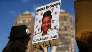 A woman at a Michael Brown memorial rally in Union Square in New York City on Aug. 9, 2015, holds a poster bearing the portrait of Sandra Bland, who killed herself in a Texas jail cell July 13, 2015.KENA BETANCUR/AFP/Getty Images