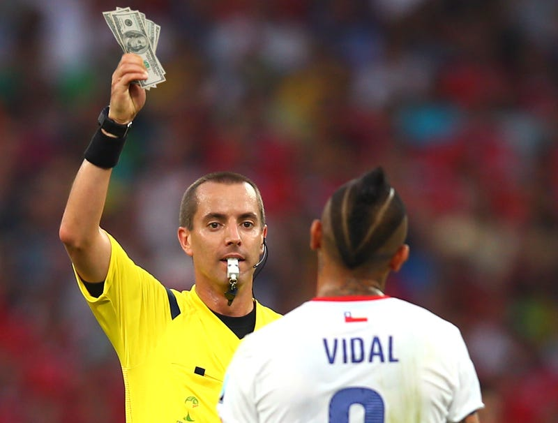 Illustration for article titled World Cup Referee Accidentally Grabs Stack Of Hundreds Instead Of Yellow Card