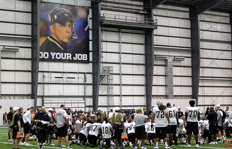 Illustration for article titled There Is A Giant Photo Of Sean Payton Watching Over Saints Training Camp