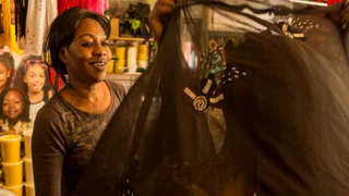 Haddi, a naturalized citizen from the Gambia, West Africa, helps a customer at her boutique in the Malcom Shabazz African Market in Harlem. Haddi, who asked to be identified by only her first name, moved with her husband to New York 27 years ago. Though she says she has a college degree and worked in a bank back home, she ended up working on a factory assembly line in the U.S.Ed Lefkowicz