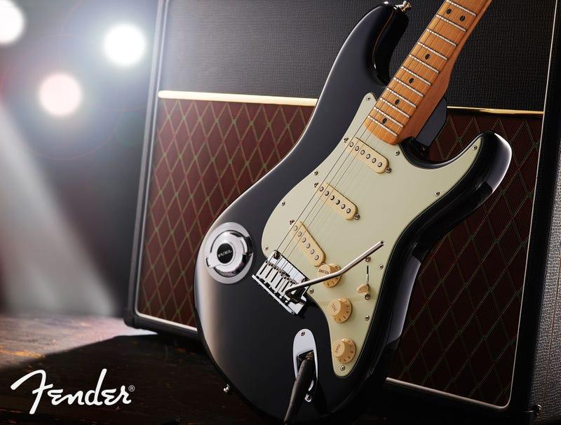 A Fender guitar sits next to an amp.
