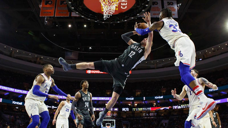 The Sixers' Robert Covington blocks the Nets' Joe Harris during last night's game.