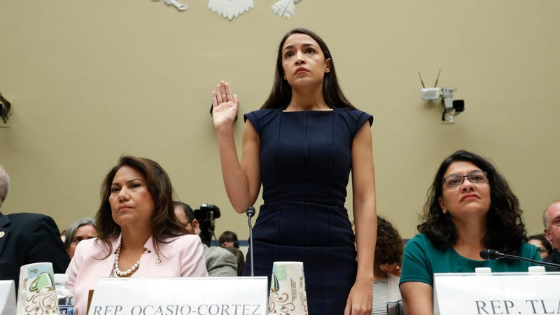 Rep. Alexandria Ocasio-Cortez (D-N.Y.) stands to be sworn in before she testifies before the House Oversight Committee hearing on family separation and detention centers, July 12, 2019, on Capitol Hill, flanked on her left by Rep. Veronica Escobar (D-Texas) and Rep. Rashida Tlaib (D-Mich.).