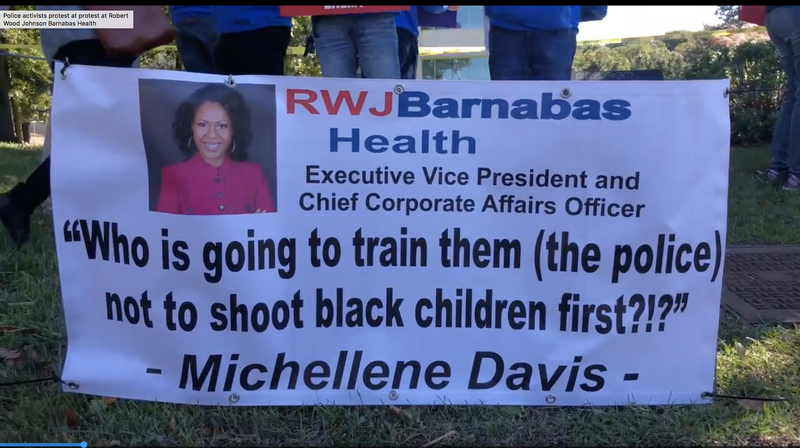 A protester holds a banner outside RWJBArnabas Health