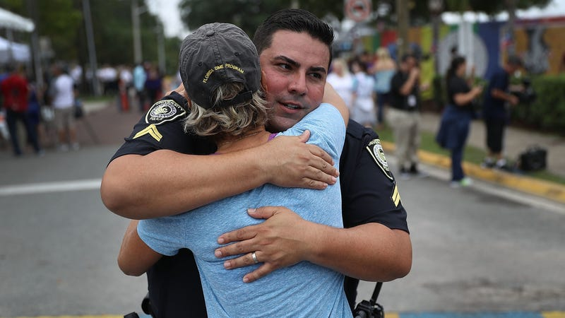 University Of Central Florida Police officer Pablo Vargas receives a hug from Christine Gigico
