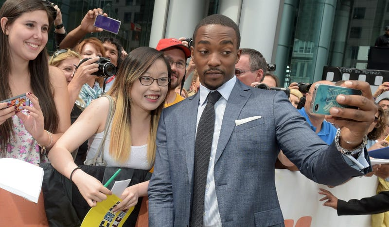 Illustration for article titled Caption This Picture of Anthony Mackie Snapping a Selfie with a Fan