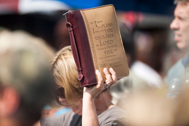 A supporter holds a bible into the air during a rally for County Clerk Kim Davis in front of the Carter County Detention Center on September 8, 2015 in Grayson, Kentucky. Image via Getty.