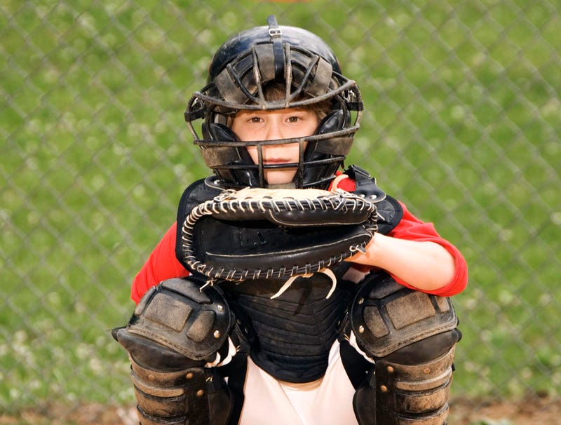 A young boy in full catcher's gear crouches at home plate.