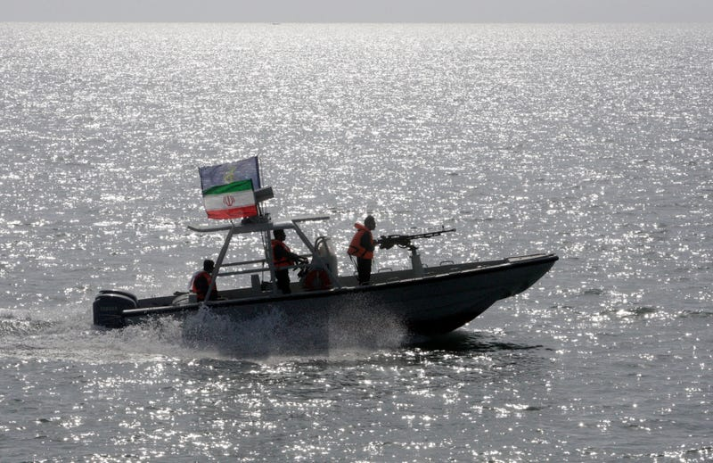 FILE- In this Monday, July 2, 2012 file photo, an Iranian Revolutionary Guard speedboat escorts a passenger ship, unseen, near the spot where an Iranian airliner was shot down by a U.S. warship 24 years ago killing 290 passengers. The U.S. Navy again has accused Iranian patrol boats of harassing an American warship in the Persian Gulf, this time with one Iranian Revolutionary Guard vessel stopping right in front of the USS Firebolt and nearly causing a collision. (AP Photo/Vahid Salemi, File)