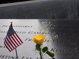 A flower and flag at the memorial to victims of the 9/11 terrorist attack at the World Trade Center in New York CityiStock