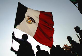 A Mexican supporter waves the national flag at the Zocalo Square in Mexico City June 21, 2006, during the transmission of the FIFA World Cup match between Mexico and Portugal.ALFREDO ESTRELLA/AFP/Getty Images