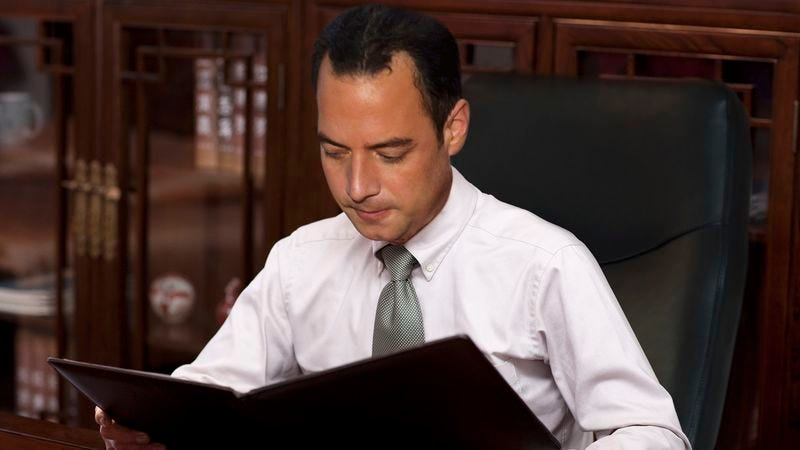 Illustration for article titled Reince Priebus Smiles, Shakes Head While Flipping Through Old Briefing On GOP's Plans For 2016