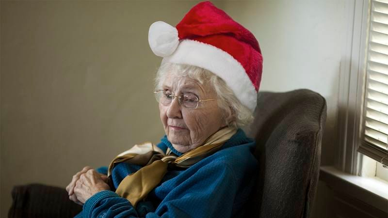 A grandma with a Santa Claus hat on.