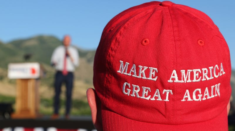 A Romney supporter listens to a speaker as he wears a 'Make America Great Again' hat at the Mitt Romney election party on June 26, 2018 in Orem, Utah.
