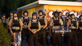 Police stand guard as demonstrators, marking the one-year anniversary of the fatal police shooting of Michael Brown, protest along West Florissant Street Aug. 10, 2015, in Ferguson, Mo.Scott Olson/Getty Images