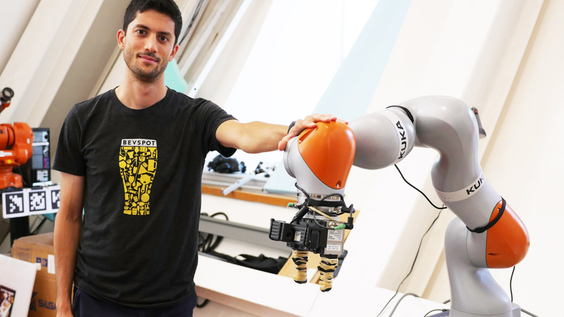 PhD student Lucas Manuelli poses with a Kuka robot arm, which uses a neural net to learn about new objects.