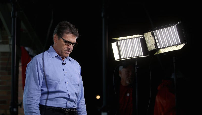 Former Texas Gov. Rick Perry enjoys a quiet moment on the campaign trail before becoming the first candidate to drop out of the Republican primary race. Image via Getty.