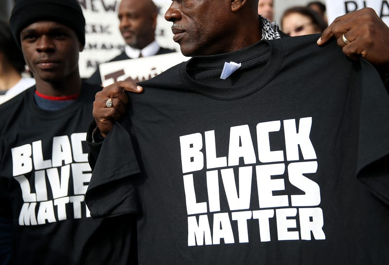 """A protester holds a Black Lives Matter T-shirt during a """"Hands Up, Don't Shoot"""" demonstration in front of the San Francisco Hall of Justice Dec. 18, 2014, in San Francisco.Justin Sullivan/Getty Images"""