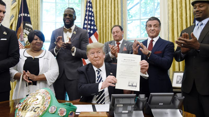 President Donald Trump holds a signed Executive Grant of Clemency for boxer Jack Johnson in the Oval Office of the White House on May 24, 2018, in Washington, D.C.