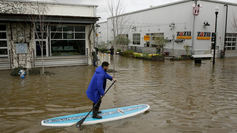 A man uses a paddle board to make his way through flooded streets in Sebastopol, California in February.