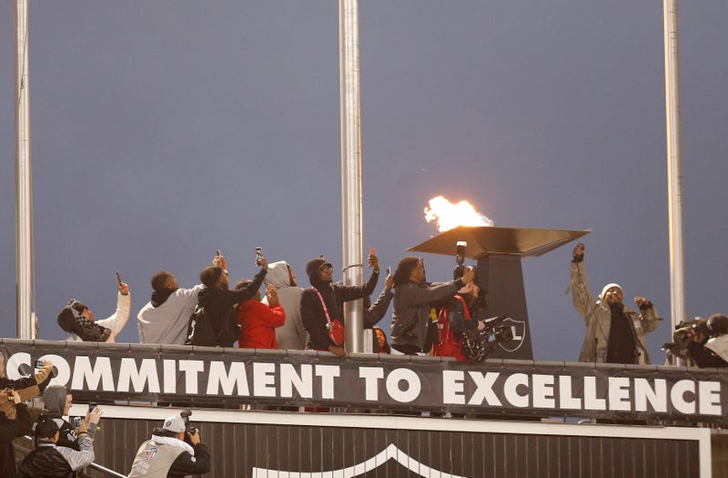 Oakland Raiders running back Marshawn Lynch, right, lights a ceremonial torch for former team owner Al Davis before an NFL football game between the Raiders and the Denver Broncos in Oakland, Calif., Monday, Dec. 24, 2018.