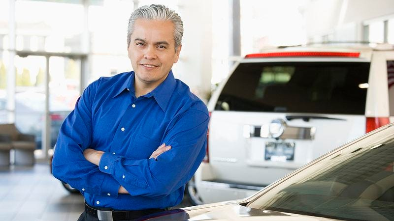 A car salesman in front of a car.
