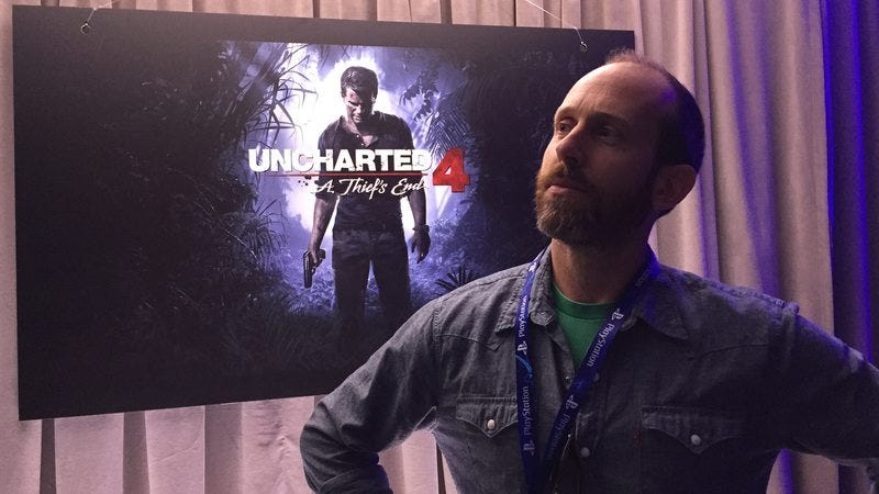 Uncharted 4 game director Bruce Straley strikes a pose in front of a poster for Nathan Drake's latest adventure.