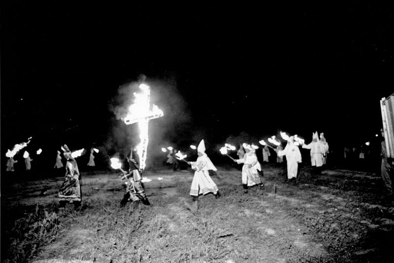 File photo of Ku Klux Klansmen carry torches and march around a large burning cross at a KKK rally in Spartanburg, S.C., Saturday, Aug. 17, 1963.  (AP Photo)