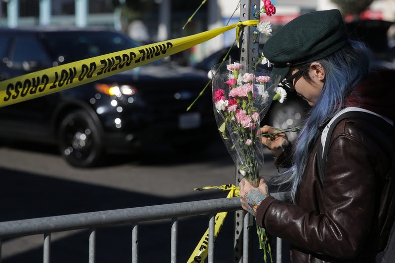 A woman places flowers on a post outside a police line  following an overnight fire that claimed the lives of at least 24 people at a warehouse in the Fruitvale neighborhood on Dec. 3, 2016, in Oakland, Calif. The warehouse was hosting an electronic music party.  Elijah Nouvelage/Getty Images