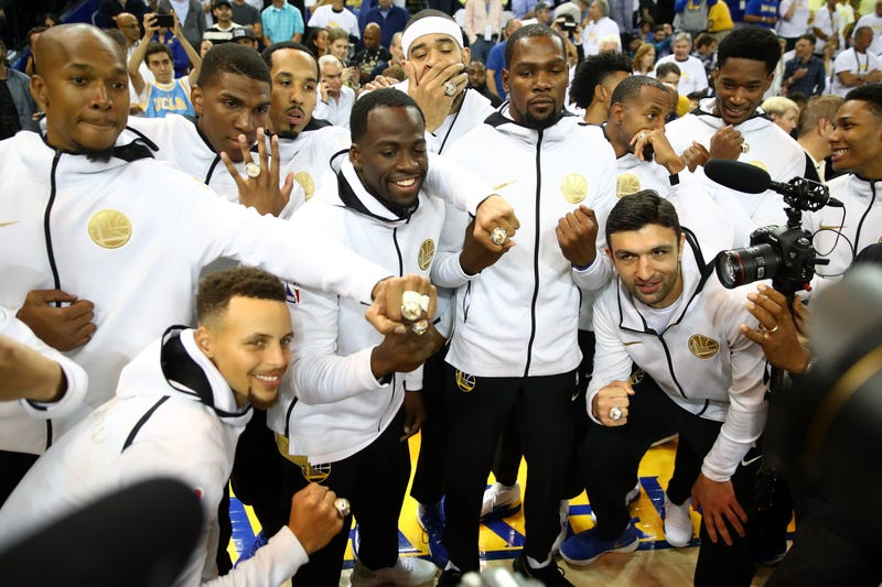 The Golden State Warriors display their 2017 NBA championship rings prior to their NBA game against the Houston Rockets at Oracle Arena on Oct. 17, 2017, in Oakland, Calif.