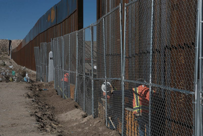 Photo of workers  raising a taller fence in the Mexico-US border separating the towns of Anapra, Mexico and Sunland Park, New Mexico via AP