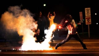 In Ferguson, Mo., a demonstrator picks up a tear gas cannister and throws it back at police four days after the Aug. 9, 2014, shooting death of Michael Brown by police.Robert Cohen/St. Louis Post-Dispatch