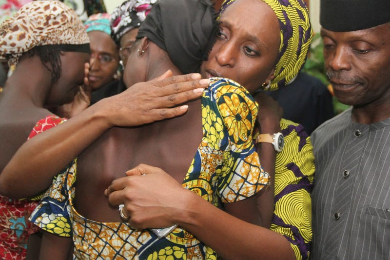 Nigerian Vice President Yemi Osinbajo (right) looks on while his wife Dolapo (center) comforts one of the 21 freed Chibok girls freed from Boko Haram, at his office in Abuja, Nigeria, Oct. 13, 2016.  PHILIP OJISUA/AFP/Getty Images