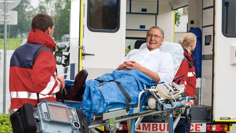 Illustration for article titled Babbling, Grinning Mitch McConnell Demands EMTs Loading Him On Stretcher Vote Yes On Healthcare Bill