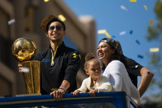 Stephen Curry of the Golden State Warriors; his elder daughter, Riley; and his wife, Ayesha, smile during a victory parade in Oakland, Calif., June 19, 2015, celebrating the Warriors' first NBA title in 40 years. Stephen Lam/Getty Images