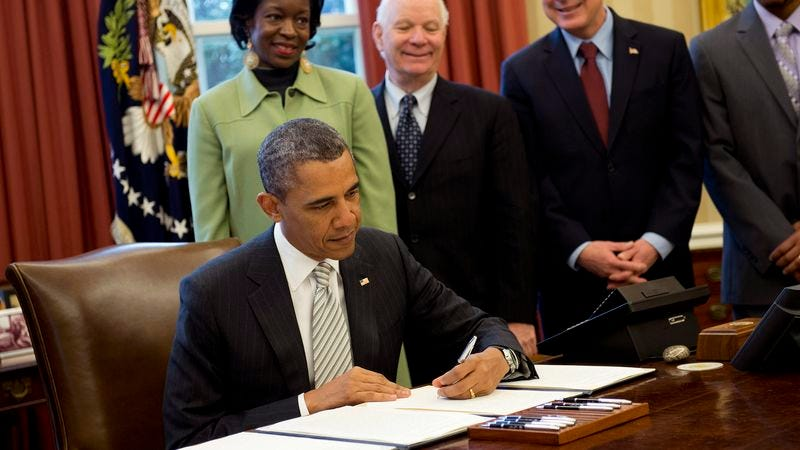 Illustration for article titled Obama Always Freaked Out By People Standing Above Him Smiling Whenever He Signs Bill