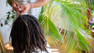 Dreadlock artist Ananda Rieber repairs and maintains a man's dread hairstyle in his flat in Berlin July 9, 2013.JOHANNES EISELE/AFP/Getty Images