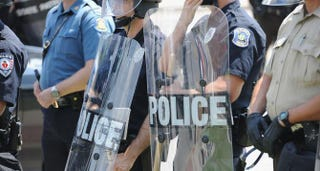 Police officers equipped in riot gear line up during a protest of the shooting death of 18-year-old Michael Brown outside Ferguson Police Department headquarters Aug. 11, 2014, in Ferguson, Mo.Michael B. Thomas/Getty Images