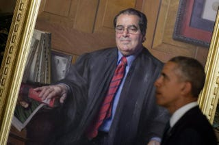 President Barack Obama passes a portrait of Justice Antonin Scalia after paying respects as Scalia's body lies in repose at the U.S. Supreme Court Building in Washington, D.C., on Feb. 19, 2016.BRENDAN SMIALOWSKI/AFP/Getty Images