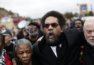 Cornel West (center), along with other demonstrators protesting the shooting death of Michael Brown, marches to the Ferguson police station in Ferguson, Mo., Oct. 13, 2014. In his response to Michael Eric Dyson's recent critique of him, West has chosen to focus on issues like Ferguson and deflect from their personal falling-out.Joshua LOTT/AFP/Getty Images