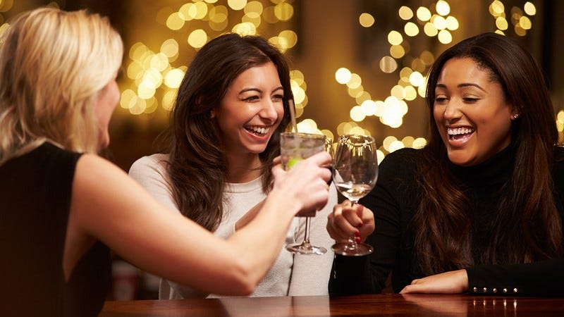 Three women enjoying a drink.