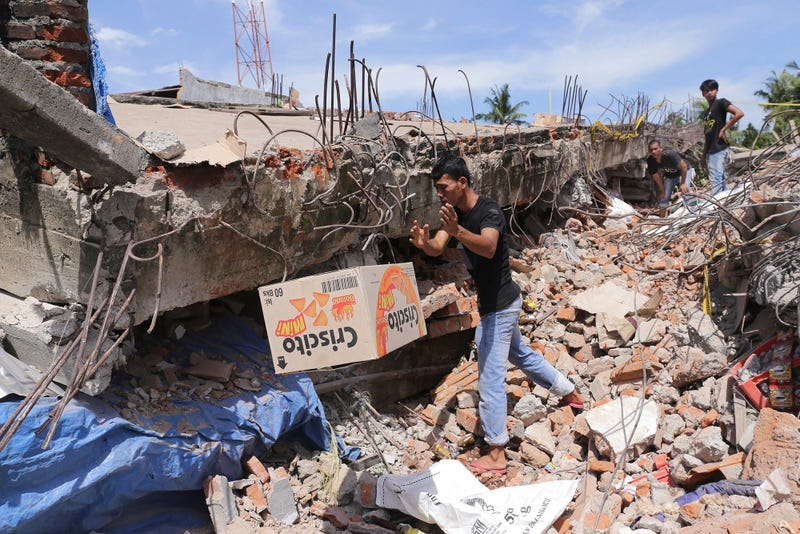 A man removes a box of food from under the rubble of a building that collapsed after the earthquake. (Image: AP/Heri Juanda)