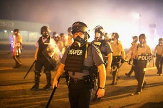 Police advance through a cloud of tear gas toward demonstrators protesting the killing of teenager Michael Brown Aug. 17, 2014, in Ferguson, Mo. Scott Olson/Getty Images