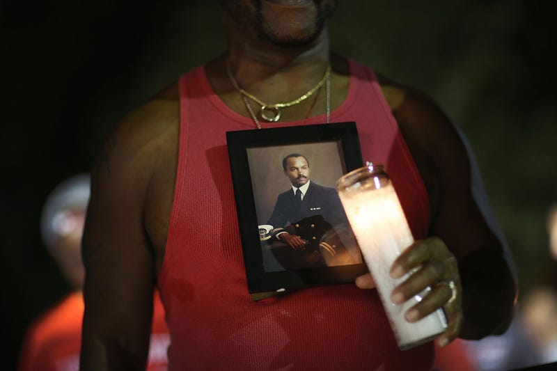 Vince Wright wears a picture of his brother Willie Wright II, who died of AIDS in 1992, as he joins with others for the Broward House and the Pride Center at Equality Park World AIDS Day Vigil and Remembrance Walk in Wilton Manors, Fla., on Dec. 1, 2015. (Joe Raedle/Getty Images)