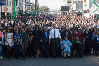From center to left: President Barack Obama; Rep. John Lewis (D-Ga.); first lady Michelle Obama; Sasha Obama; Michelle Obama's mother, Marian Robinson; and Malia Obama at the front of the crowd in Selma, Ala., March 7, 2015The White House