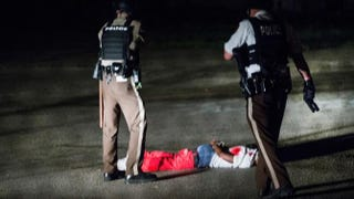Police come upon a man lying in a parking lot with what appears to be gunshot wounds after a barrage of gunfire erupted along West Florissant Avenue in Ferguson, Mo., during a demonstration Aug. 9, 2015, to mark the one-year anniversary of the police shooting of Michael Brown.Scott Olson/Getty Images